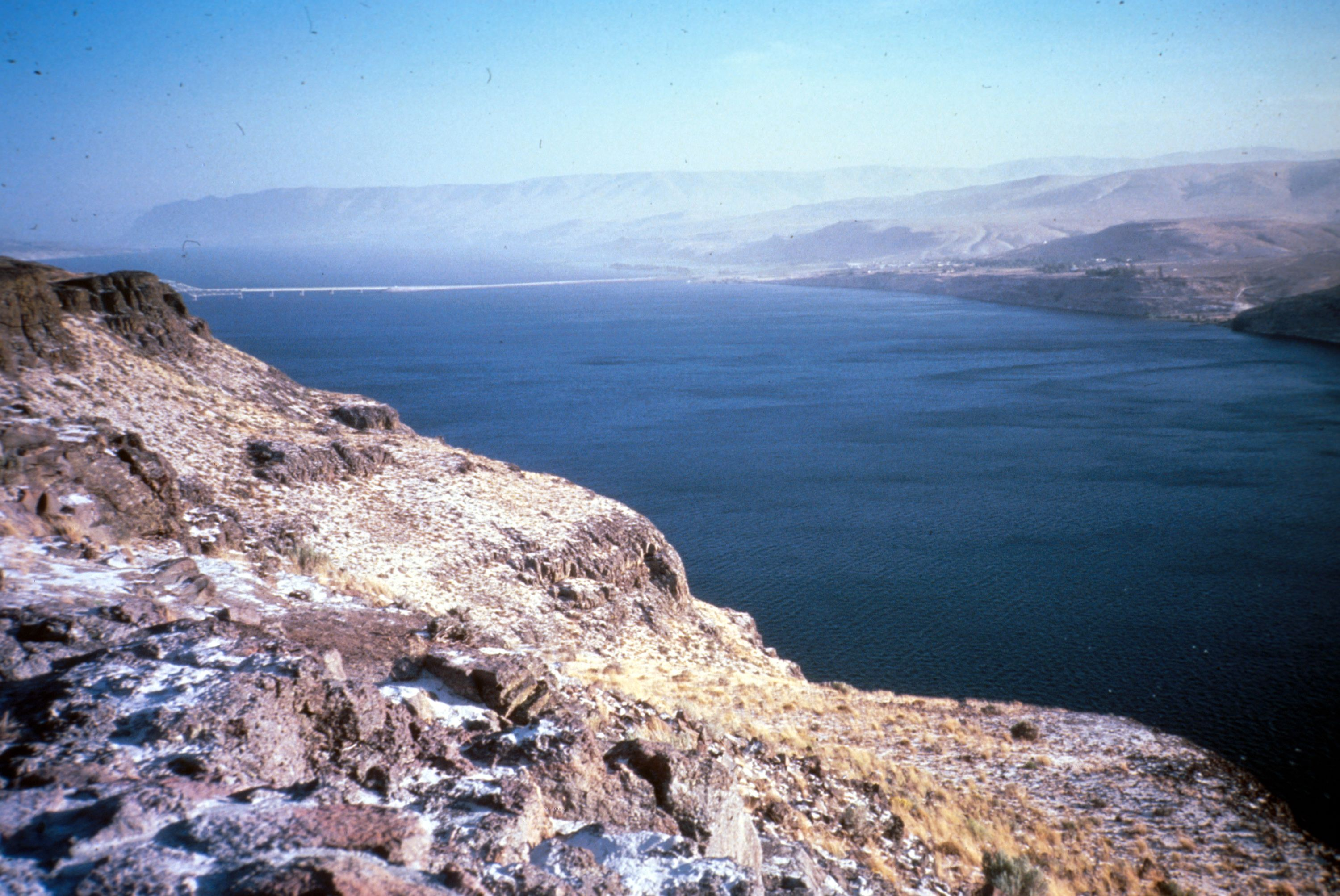 Image shows a portion of the Columbia River. The river is dark blue. There is a screen of ash drifting over it in the background of the photo, making the distance all hazy, almost like cirrus clouds close to the ground. The weathered brown basalt of its banks is dusted with whitish-gray ash, almost looking like a fine coating of snow.