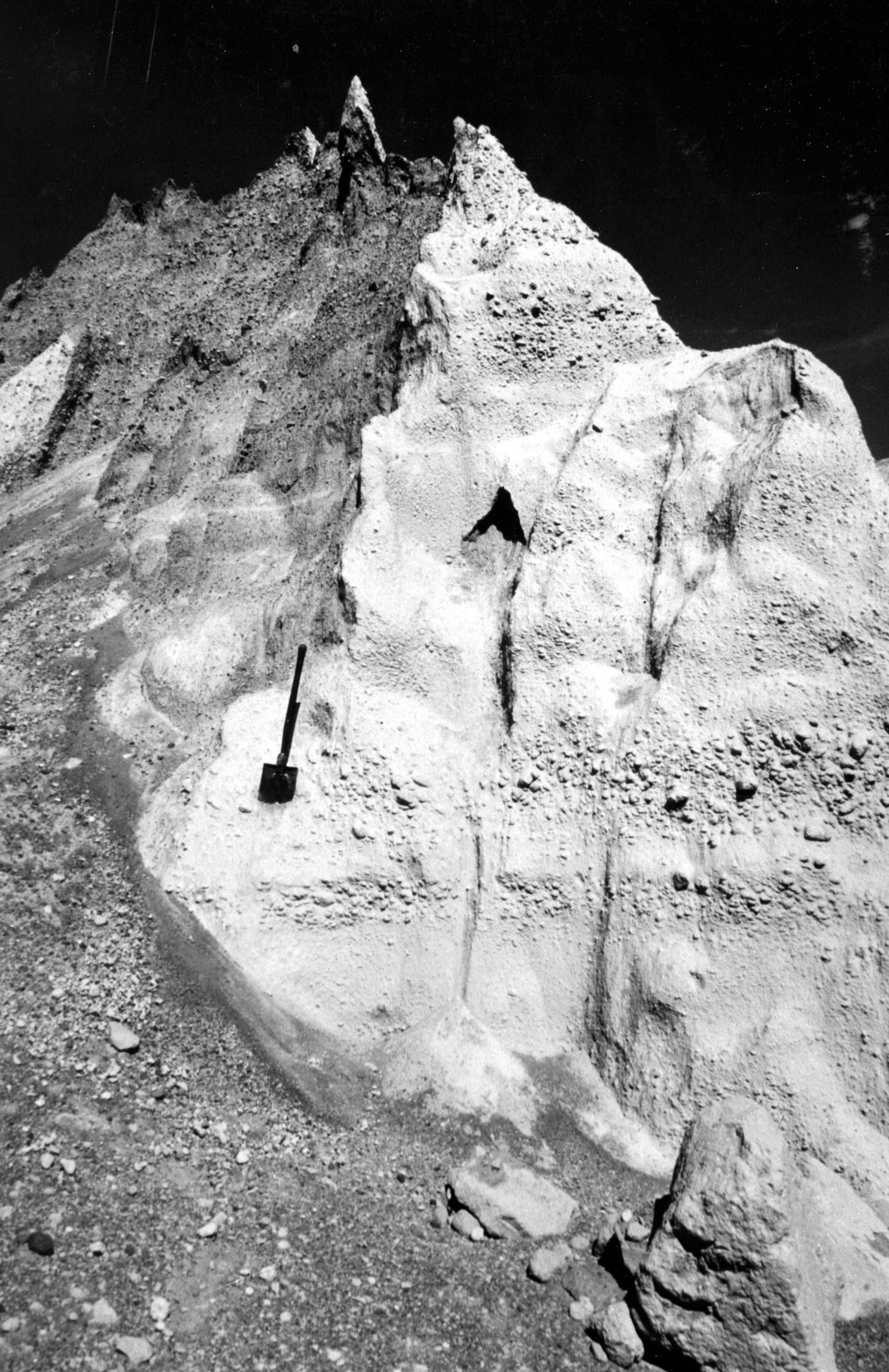 Black and white image shows a jagged ridge of deposits with a shovel for scale. The deposits are layered with fine and coarse layers.