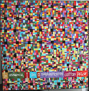 "A quilt made of colorful rectangles with the text ""In essence, I am a sophisticated cotton picker"" at the bottom."