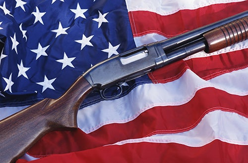 gun on top of American flag