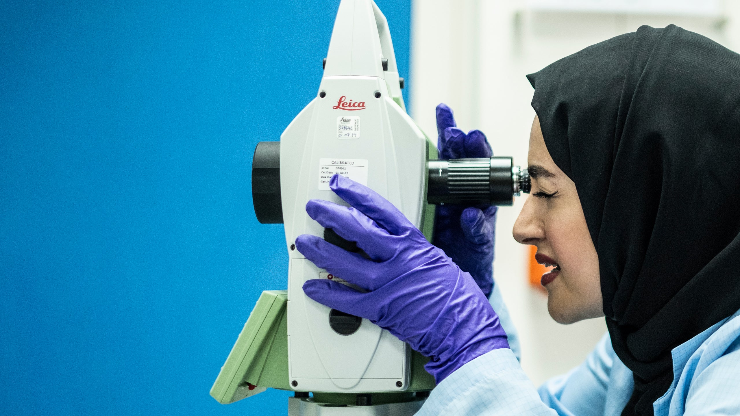 Muna al Hammadi looks through the viewfinder of a measuring machine