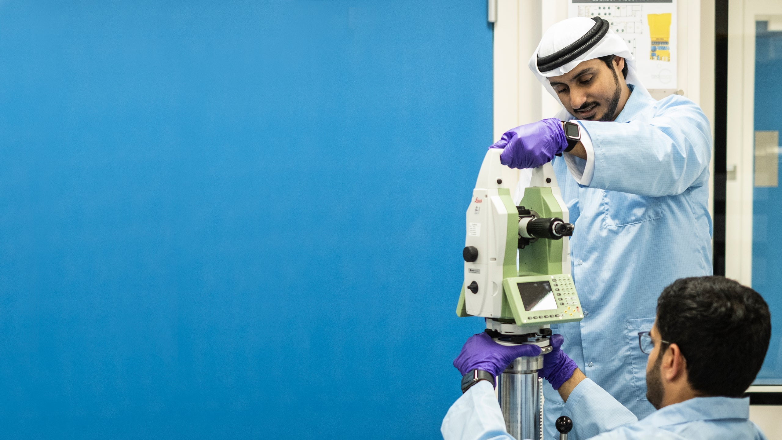 Muna al Hammadi watches Ali al Suwaidi and Mahmood Alawadhi adjust a measuring device in a lab