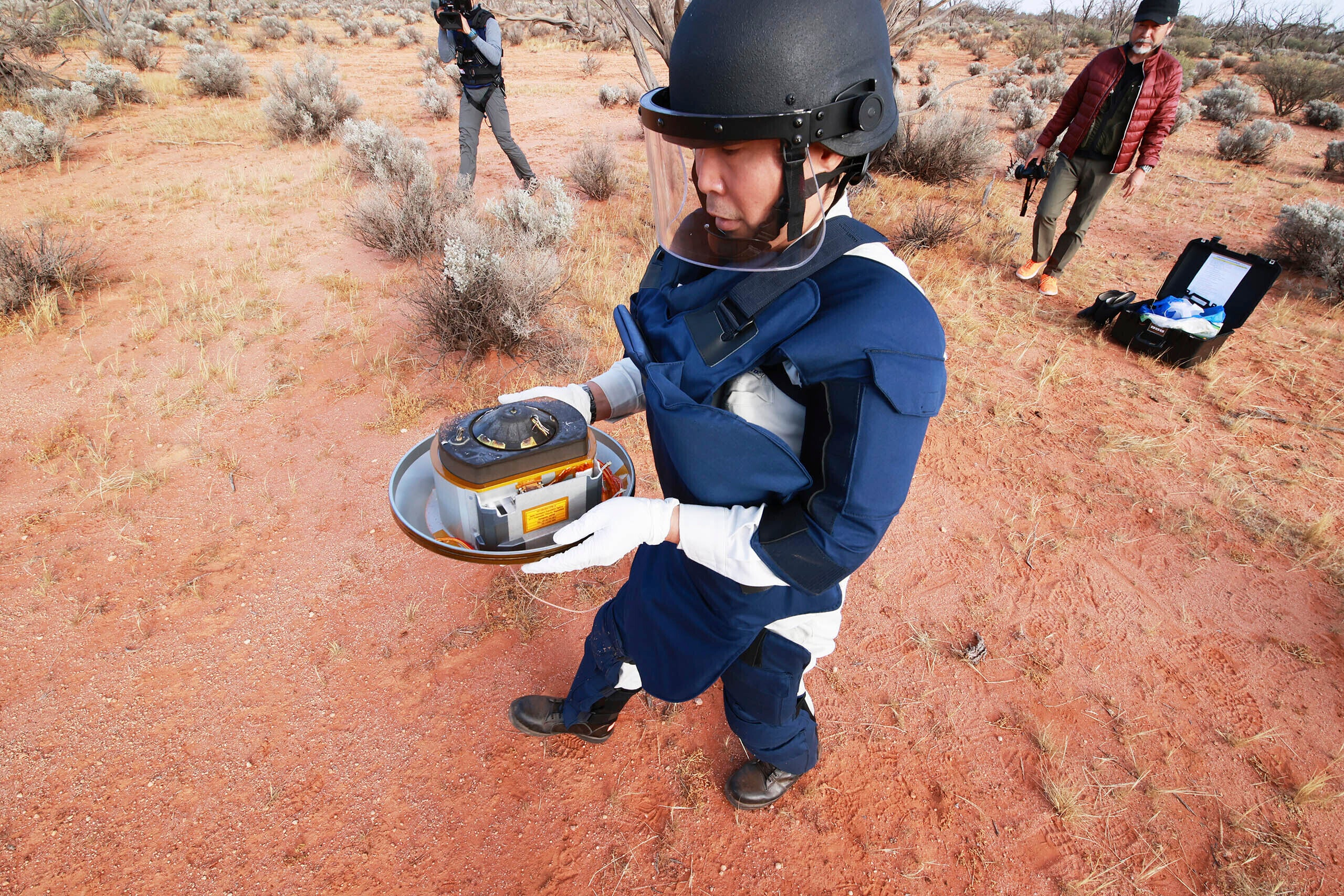 Member of the Hayabusa2 team holds the mission's sample-return capsule
