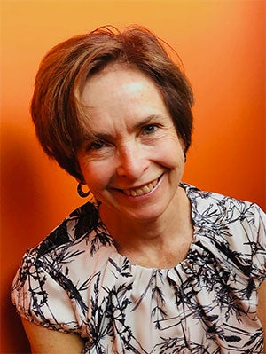 A smiling Sue Smrekar against an orange background.
