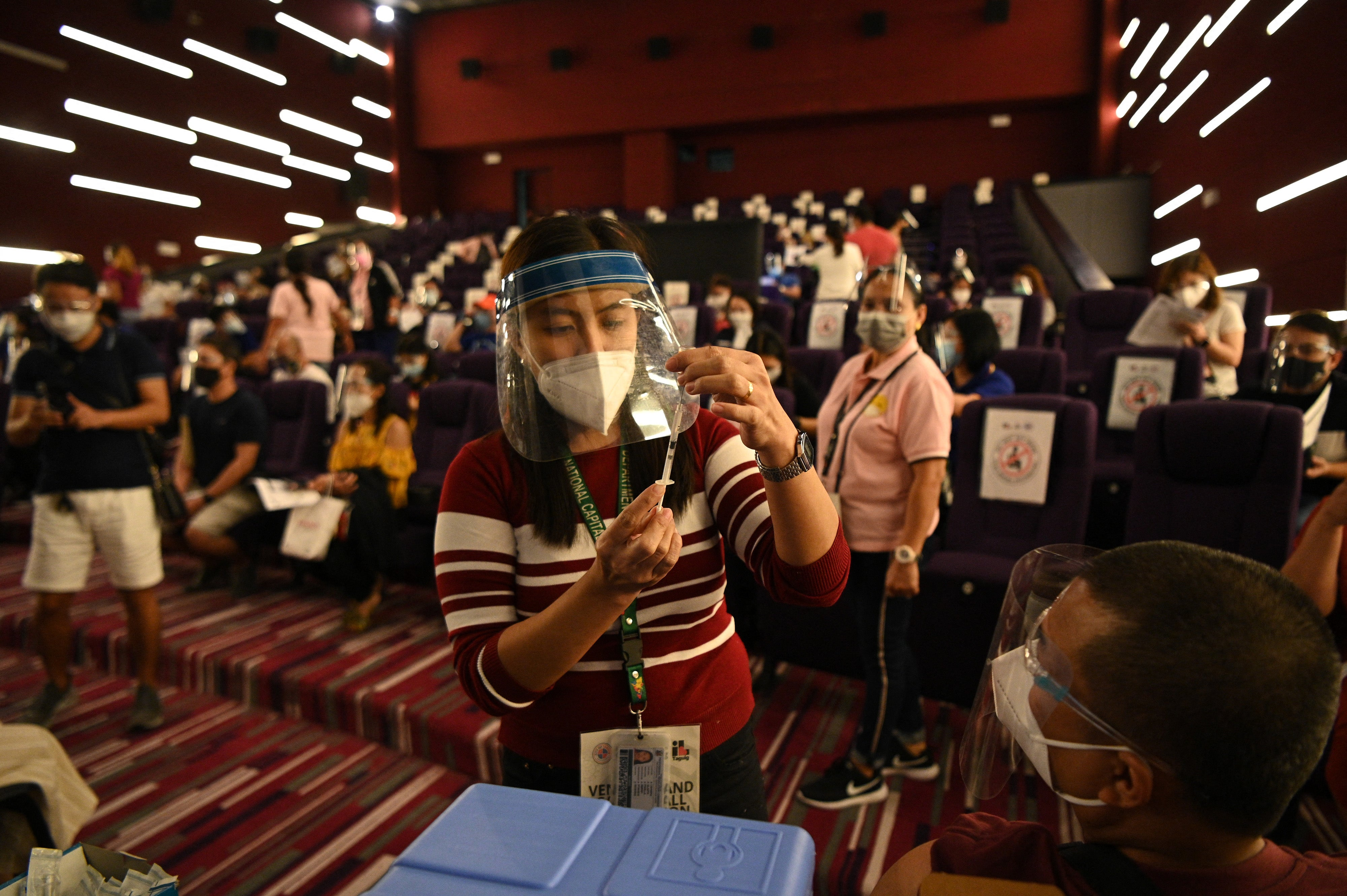A health worker prepares a vial of Chinese Sinovac vaccine against Covid-19 coronavirus disease inside a movie theatre turned into a vaccination centre in Taguig City suburban Manila on June 14, 2021.