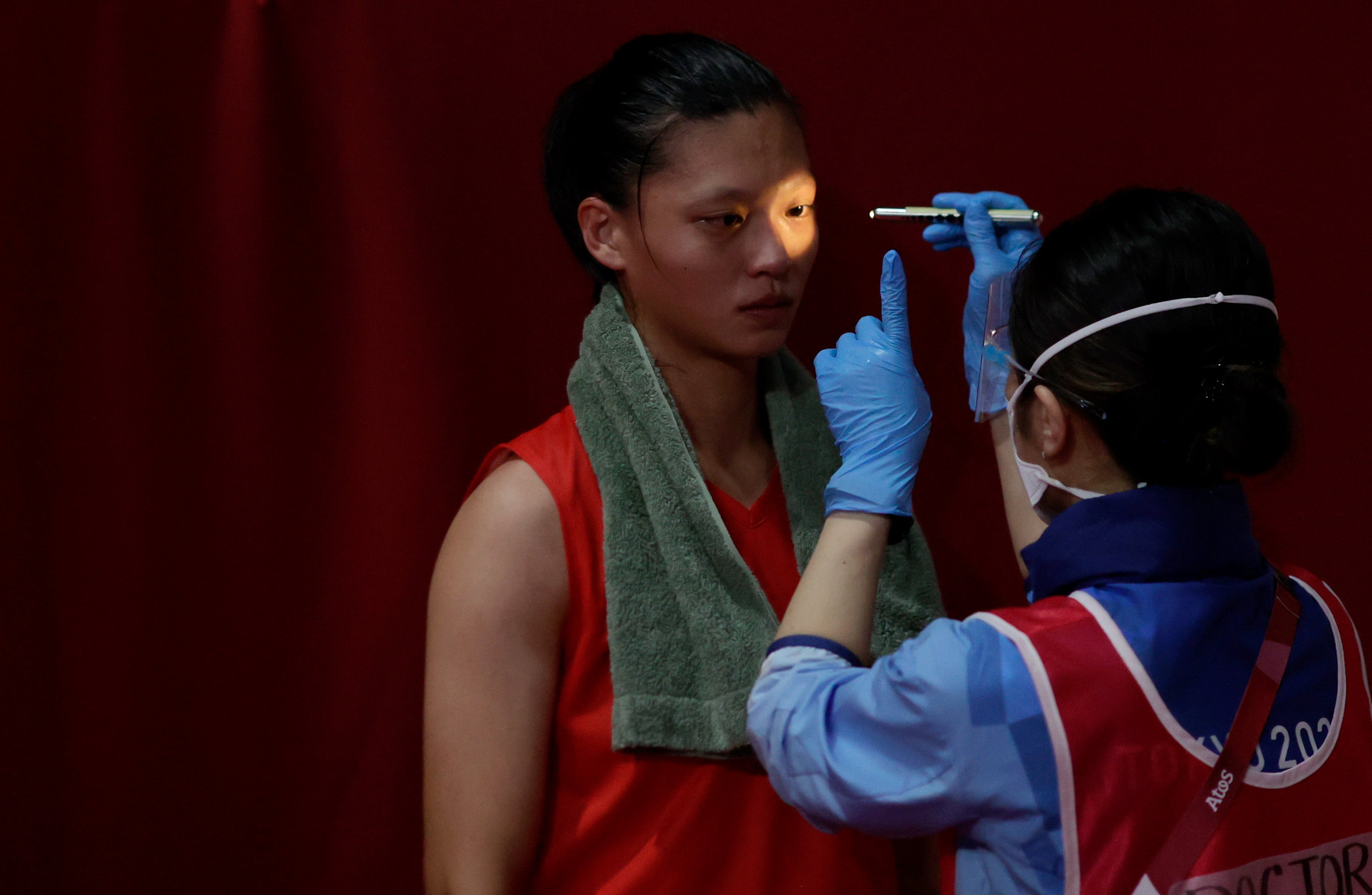 A doctor examines an athlete for injuries during a boxing match at the Tokyo Olympics in July 2021.