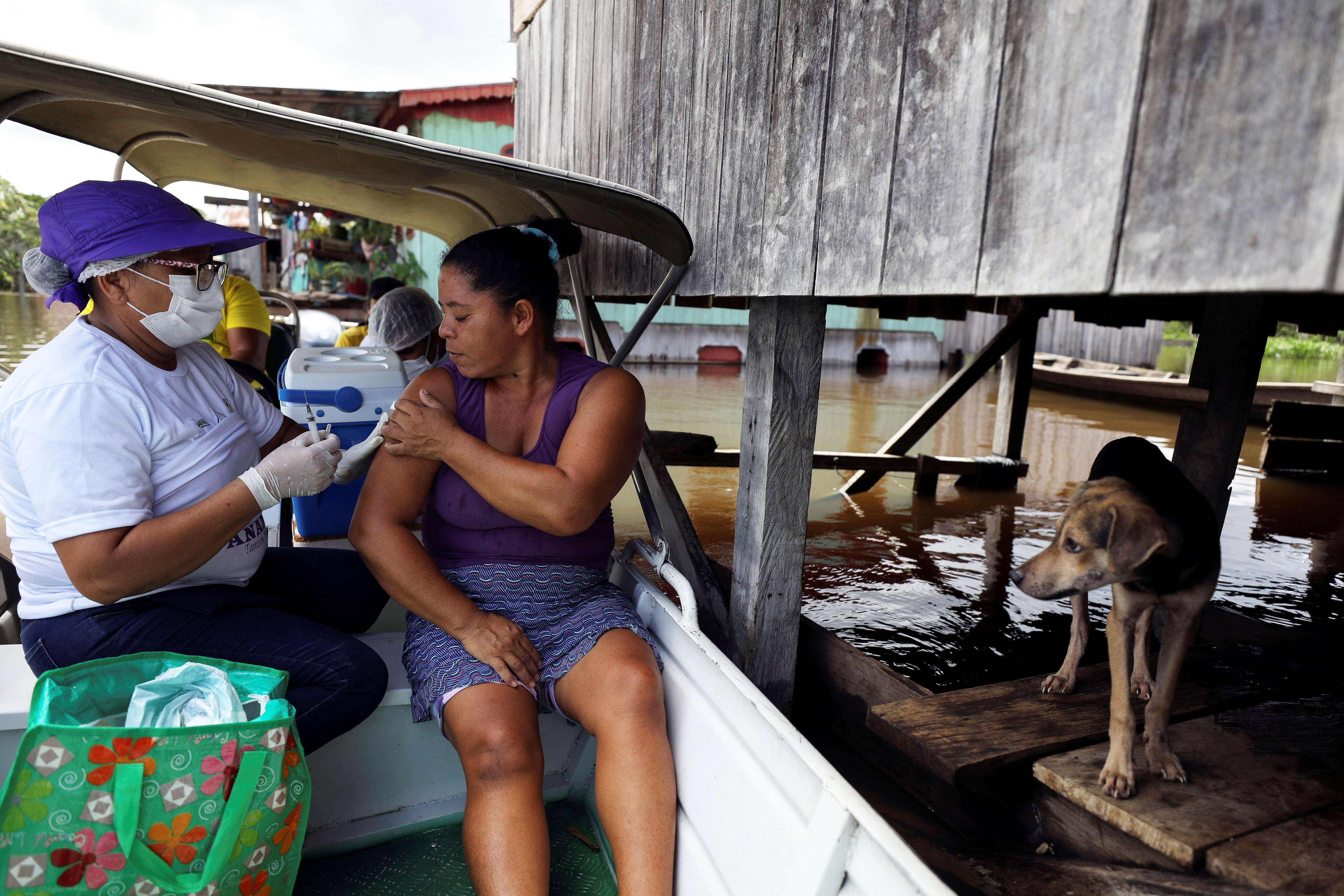 Health worker administers doses of the Oxford–AstraZeneca vaccine on a boat by the Amazon River in Brazil during a flood.
