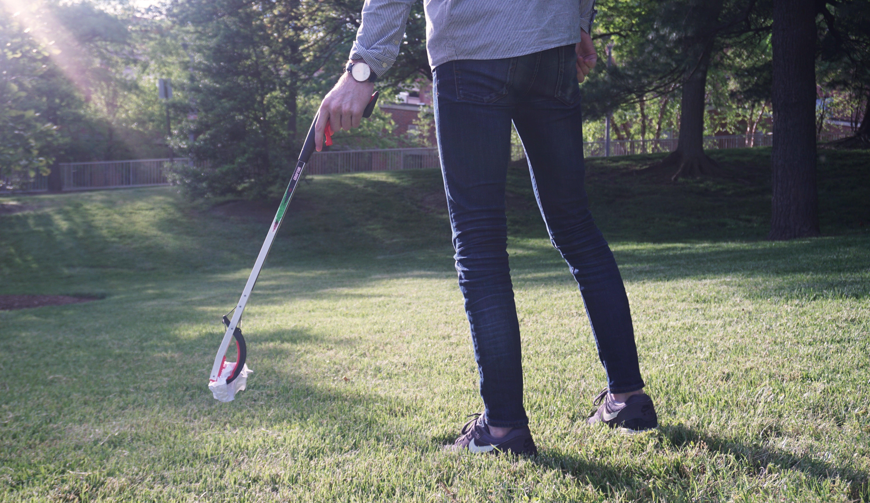 Man holding a litter picker tool at a park.