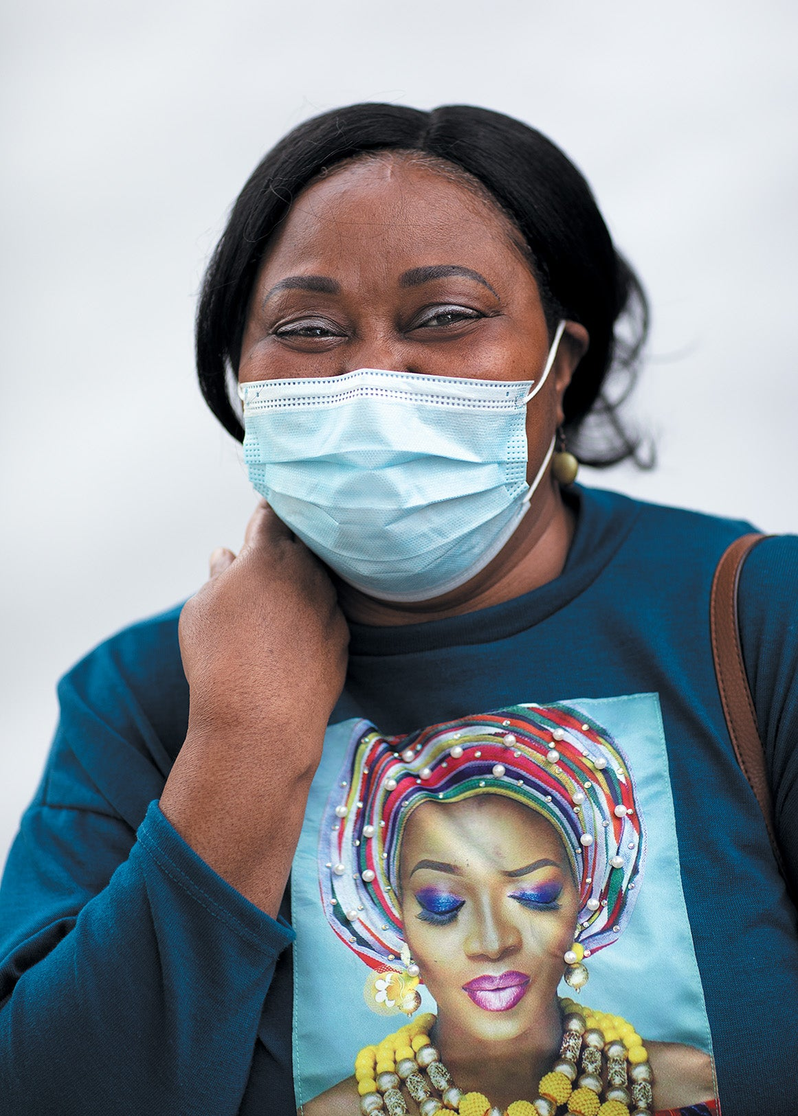 Youlanda Lee-Clendenen smiles while wearing a face mask standing against white background.