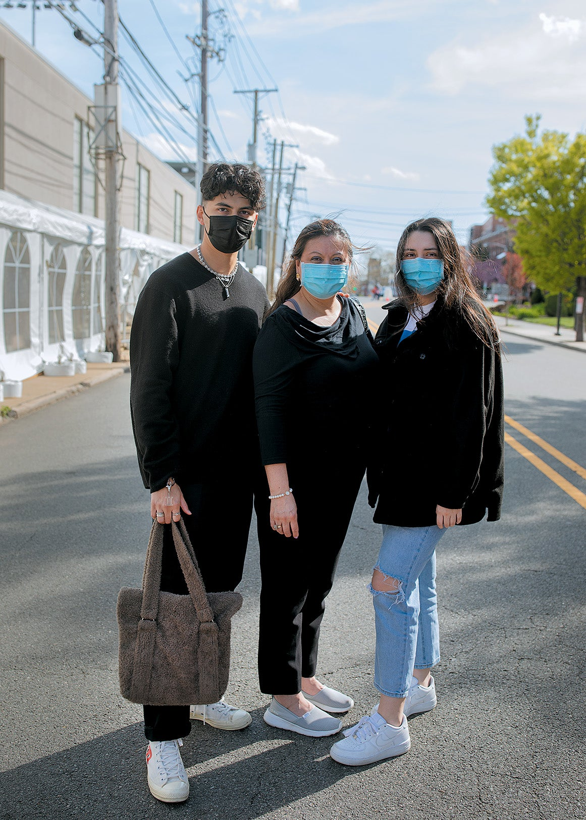 Three people wearing face masks and black clothing posing together on the street.