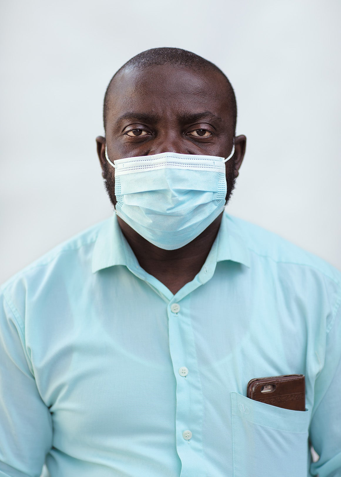 Alex Appiah Frimpong wears a blue shirt and face mask.
