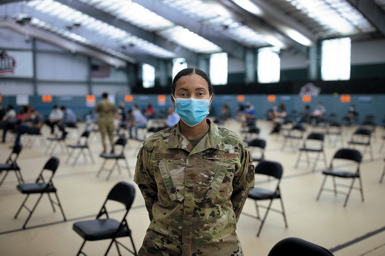 The Air Force doctor and colonel, Cecilia Sessions, is wearing military uniform and face mask and is standing in the vaccination center.