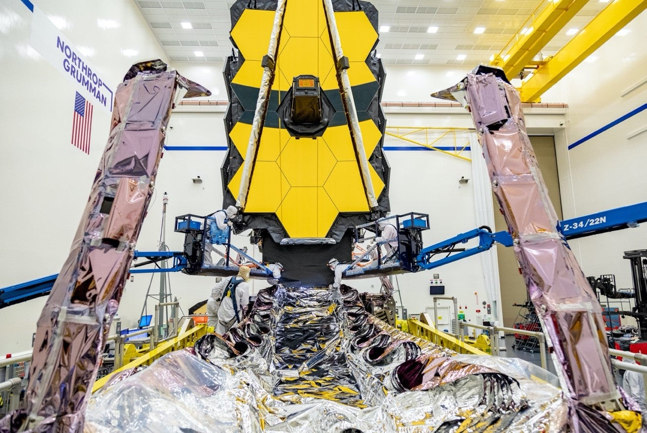 Technicians examine the James Webb Space Telescope in preparation for its launch.