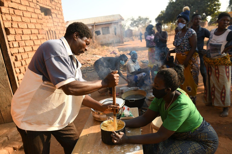 Winston Zgambo helps Anita Chitaya prepare bean-flour doughnuts.