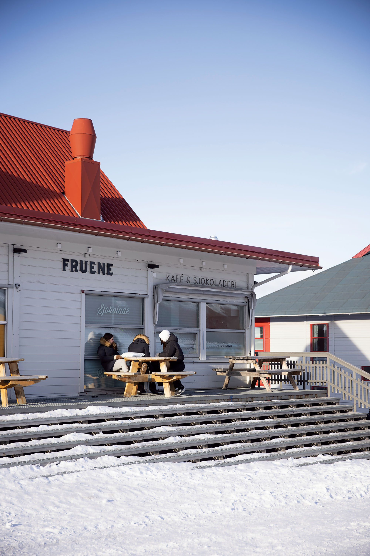 Three people wearing coats sitting outside of the Fruene cafe.