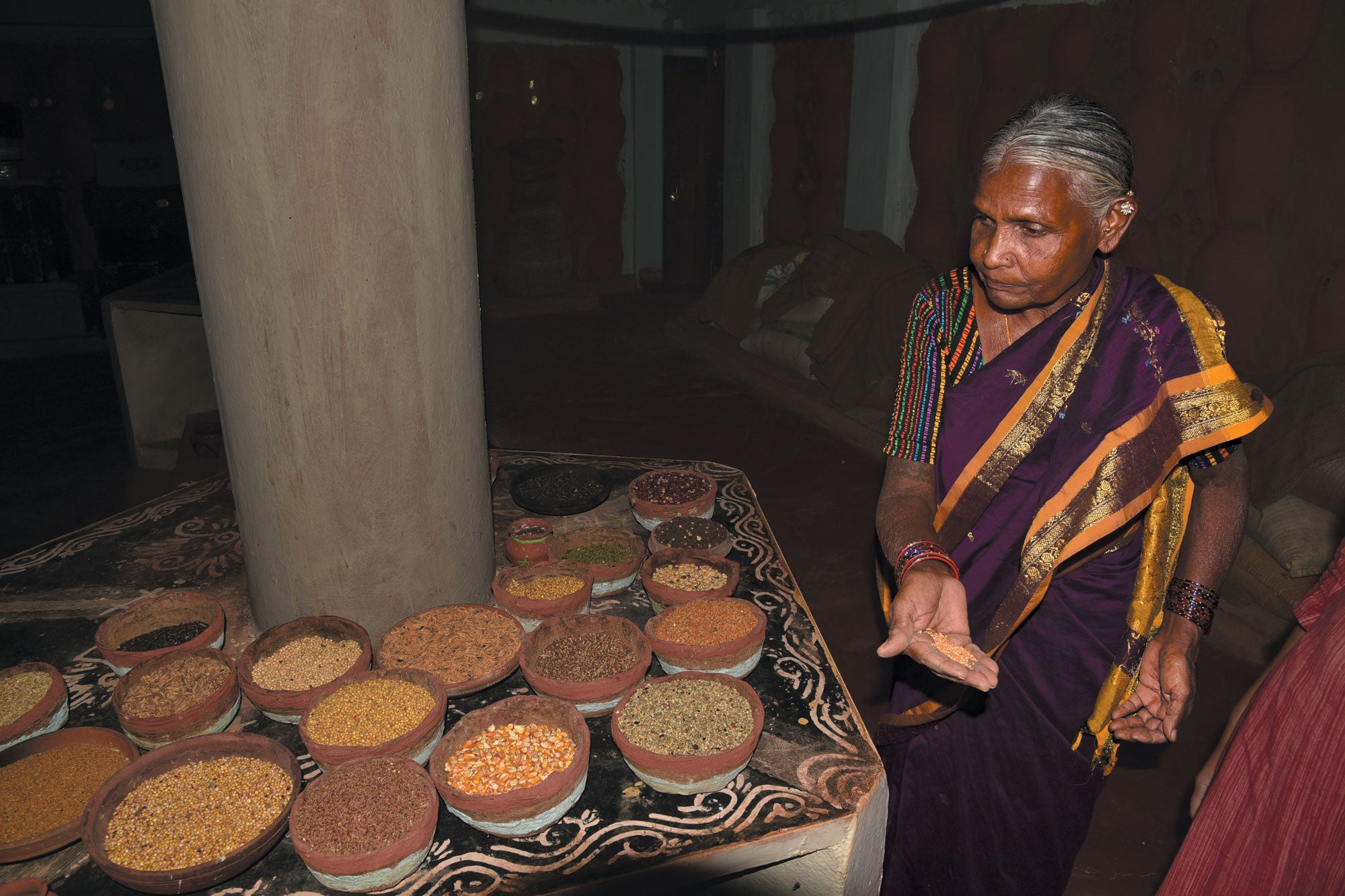 Woman showing handful of seeds selected from one of the containers on the table in front of here.