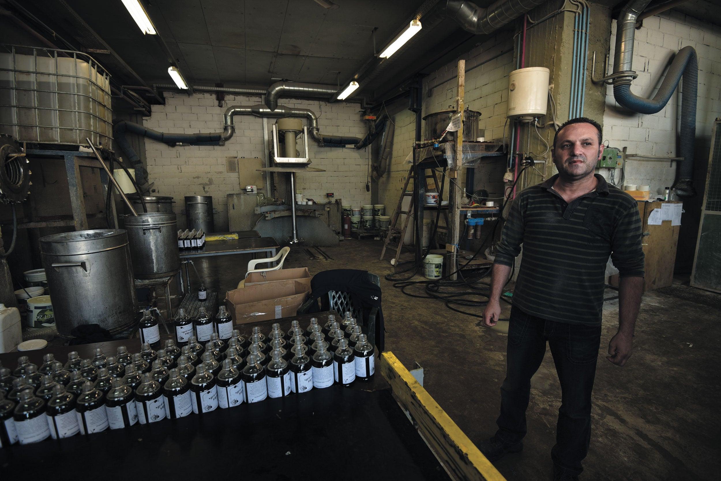 Dimitris Koumatsioulis standing inside a an eco-friendly detergent factory in Thessaloniki, Greece.