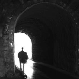 silhouette walking toward light from dark tunnel