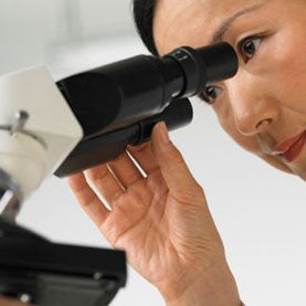 Woman looking into microscope.