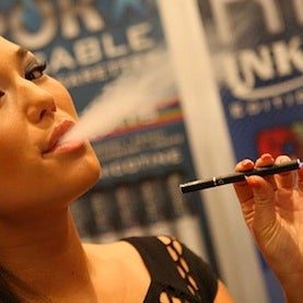 woman puffs electronic cigarette