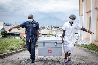 Healthcare workers cary vaccines in Goma