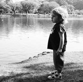 Small boy standing at a pond.