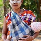 Ma Khit Shin, a Karen refugee mother bringing her infant for a check up at the Wang Pha Clinic operated by the SMRU. She wears Tanaka tree bark paste, a cooling and sun blocking paste.