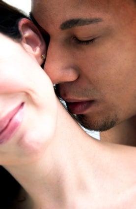 Man sensuously smelling woman's neck