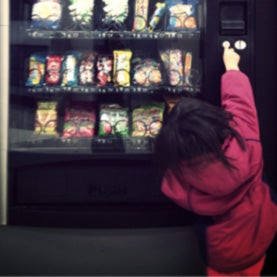 Child reaching up to vending machine.