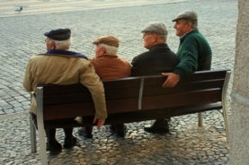 image of four men sitting on a bench, looking off in the distance