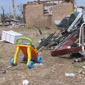 A child toy sits alone outside of a home destroyed by the tornado that struck Granbury, TX on May 15, 2013