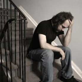 Man sits on stairwell looking depressed