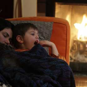 mother and son resting on the couch by the fire