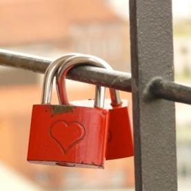 Two locks on a fence with a heart on each.