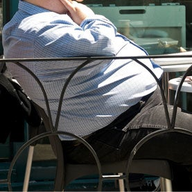 Overweight man sitting in an outdoor cafe.