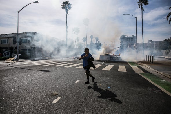 A protester runs from tear gas launched from police near the California Incline during a protest against the killing of George Floyd. Protesters took to the streets of Los Angeles for the fifth day in a row in a stance against the killing of George Floyd by former Minneapolis police officer, Derek Chauvin. Credit: Stanton Sharpe Getty Images