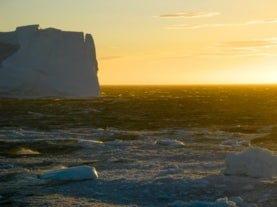 image of an ocean and an iceberg with a setting sun on the horizon
