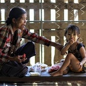A grandmother babysits her granddaughter while the girl's mother, Blu Nay L'Paw, works as a clinician in the Shoklo Malaria Research Unit (SMRU) at Mae Sot, Thailand, near the Myanmar border.