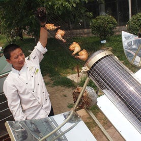 chinese chef pulling chickens from a solar powered oven