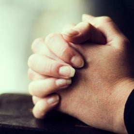 Folding hands over a bible